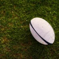 A white and black rubgy ball lying on dark green grass