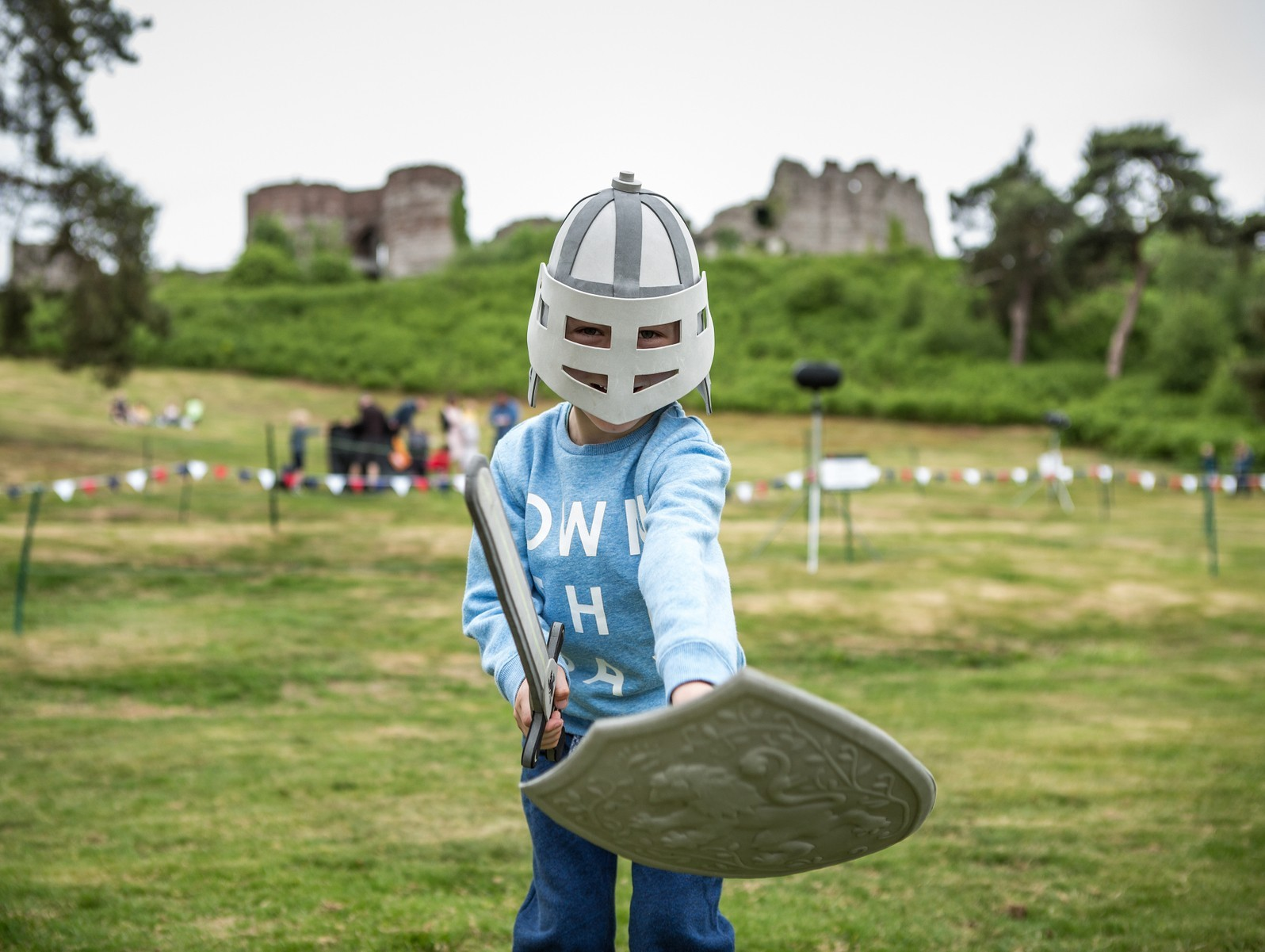Young boy in helmet holding pretend sword and shield
