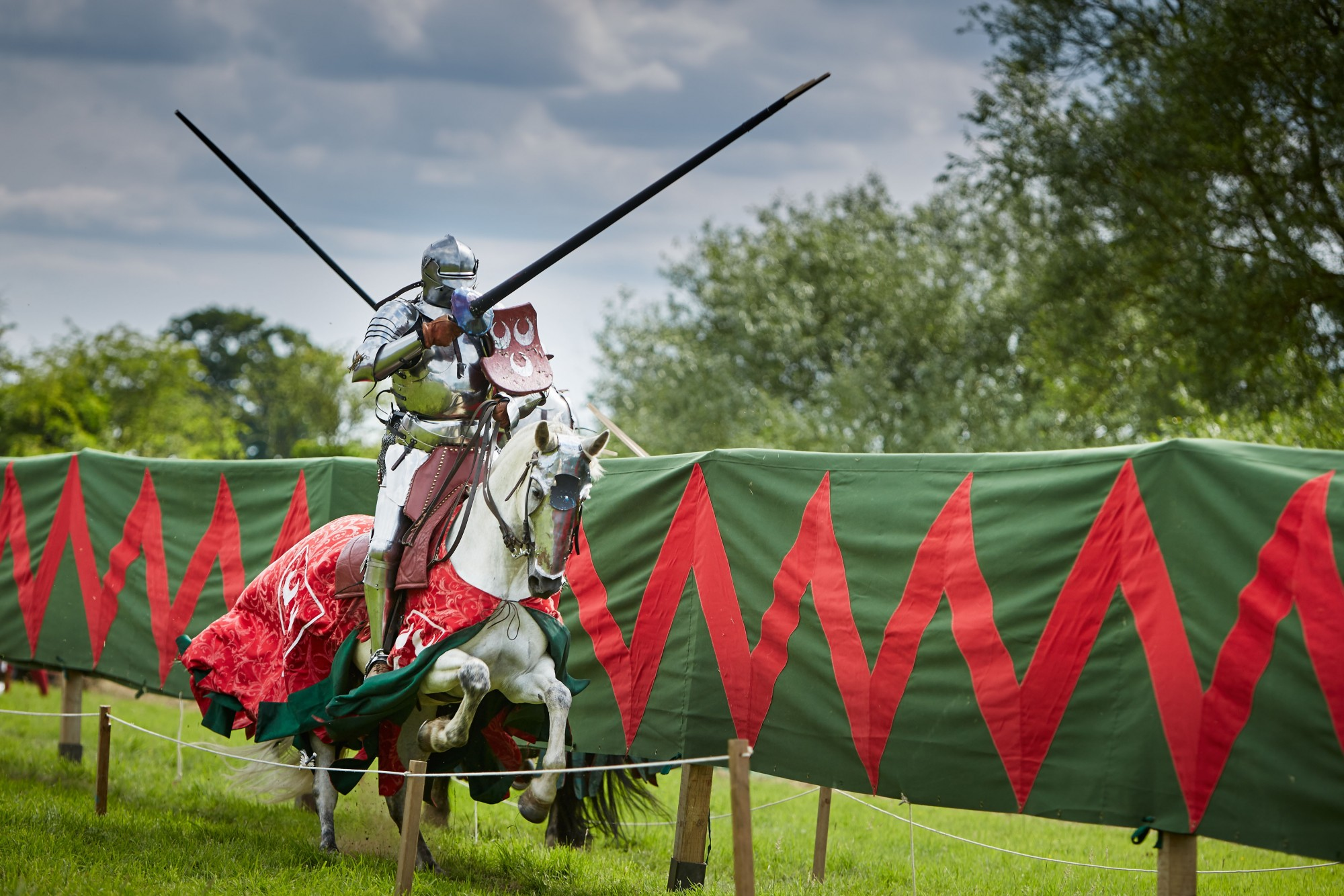 A man jousting on horseback at an english heritage site
