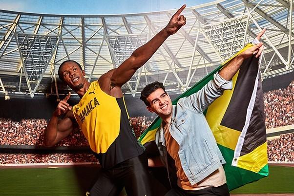 Man with Jamaican flag posing with waxwork Usain Bolt