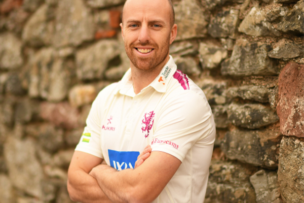 Jack leach with his arms folded smiling for the camera