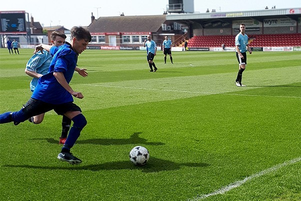 Footballers on a grass pitch