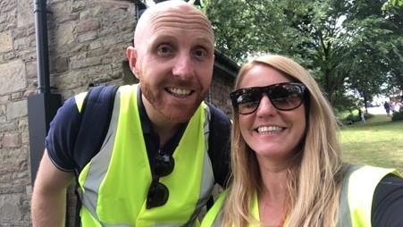 Selfie photo of two people dressed in high-vis jackets