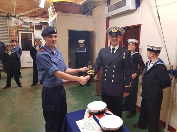 Two men shaking hands in sea cadet uniform