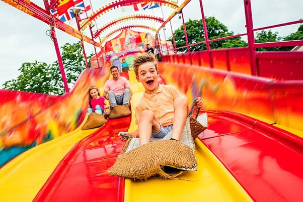 young boy in a sack racing down giant slide