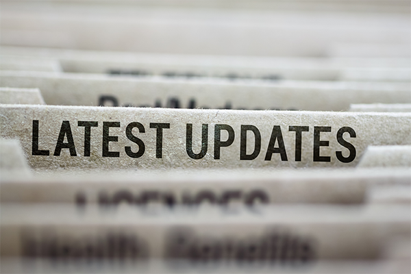 Paper file folders in a filing cabinet with a folder called 'latest updates' in the centre