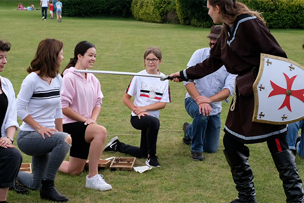 A little girl being knighted during an adventure out game