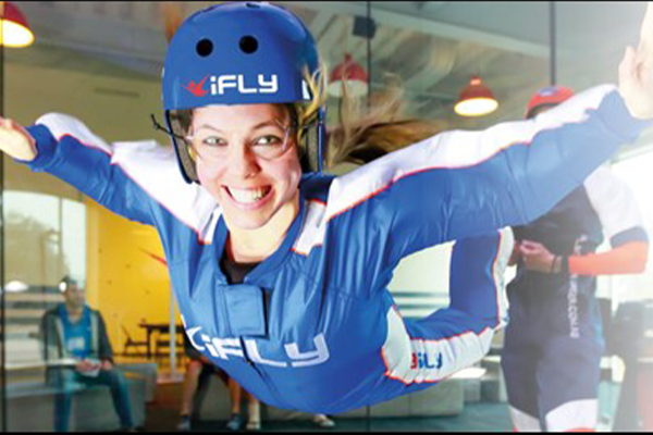 A woman smiling at the camera whilst indoor skydiving
