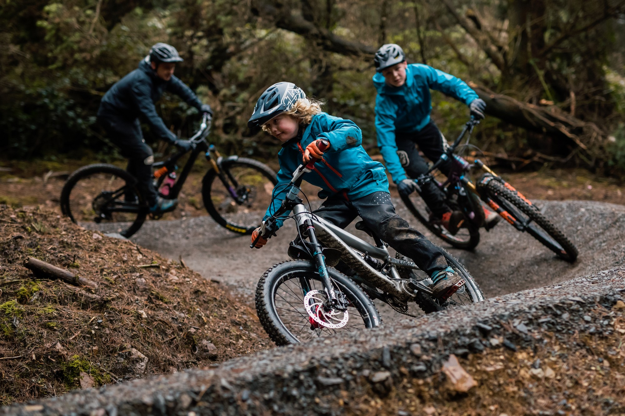 Kids and adults riding down a beginners mountain bike trail at bikepark wales