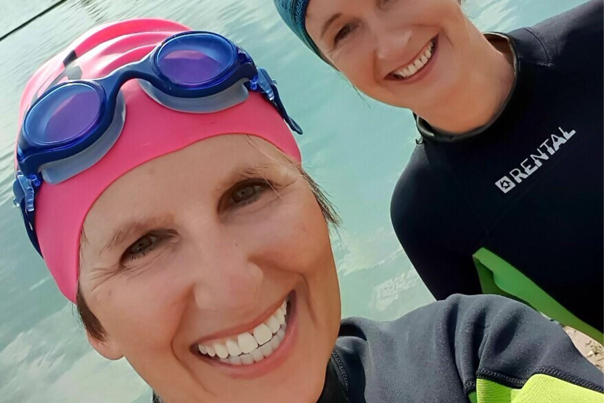 Two women in open water swimming gear
