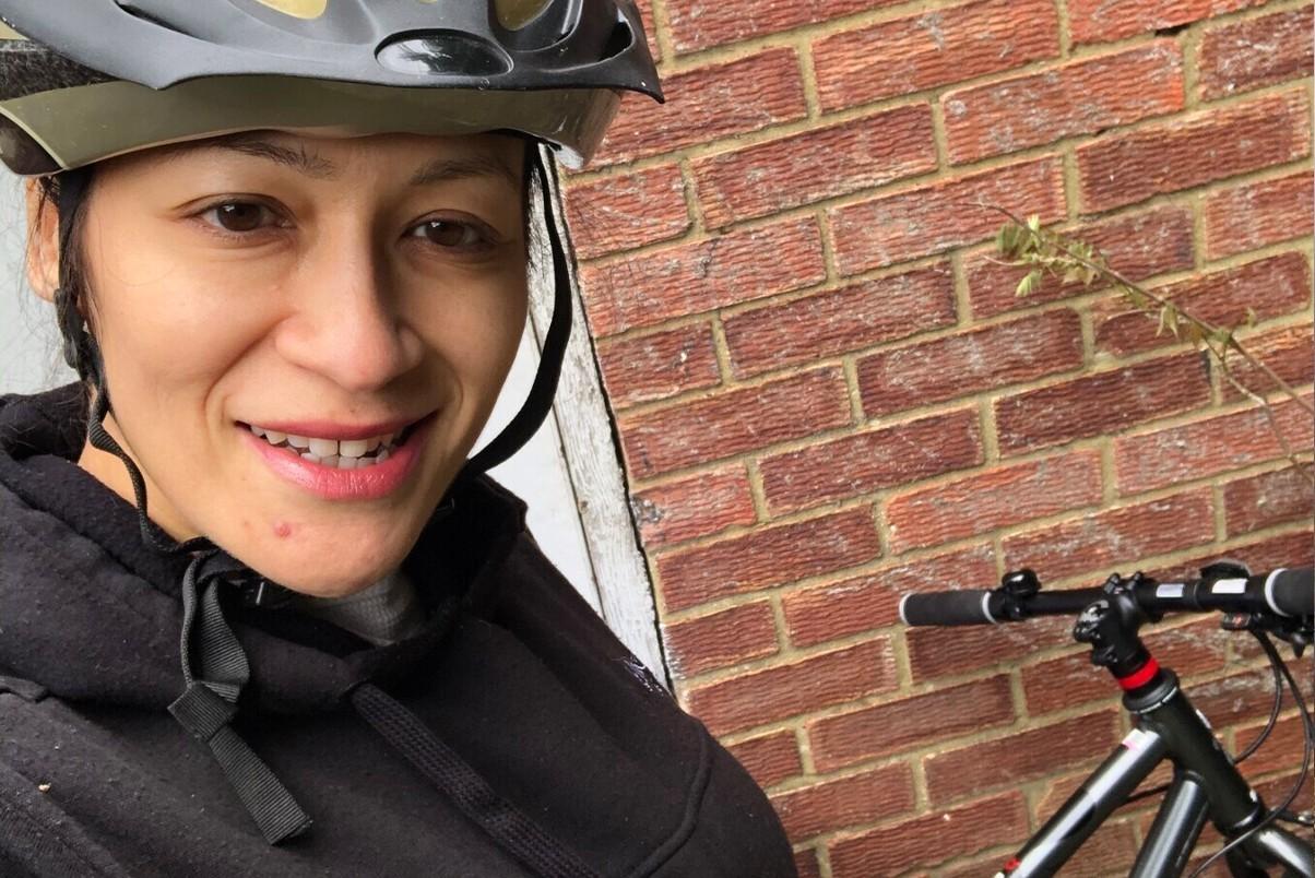 Woman stood in front of a bike wearing a helmet