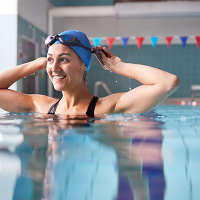 A woman smiling while adjusting her goggles in a swimming pool