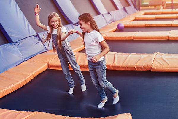 Two girls holding hands and jumping on a trampoline