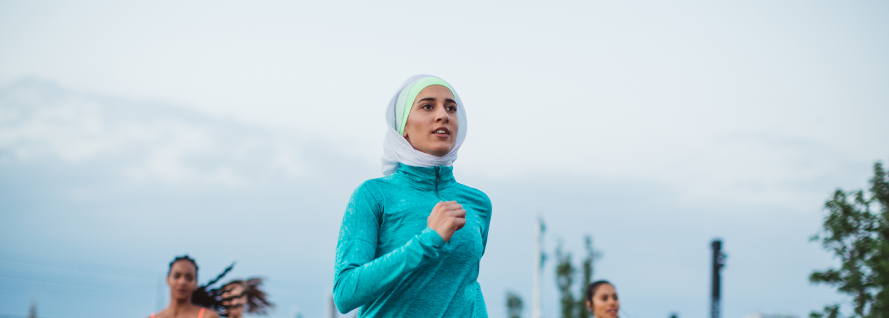 A woman running outside wearing activewear and a hijab