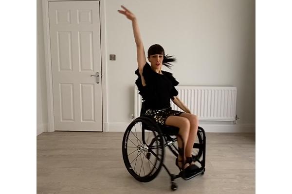 A lady in a wheelchair dancing at home