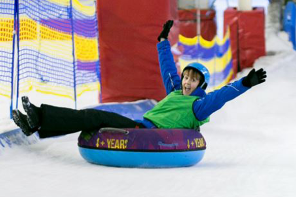 A kid cheering as he rides a donut down the snow slope