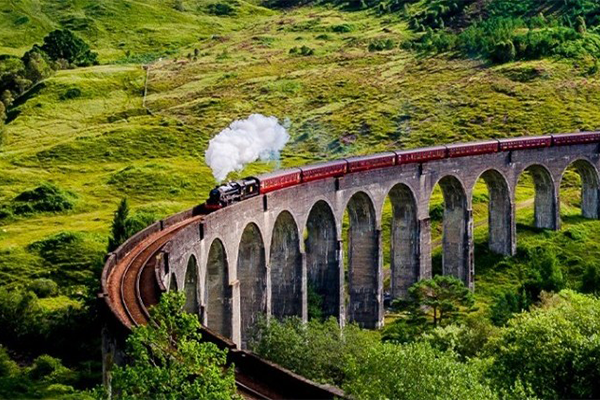 A train traveling across a viaduct in Scotland