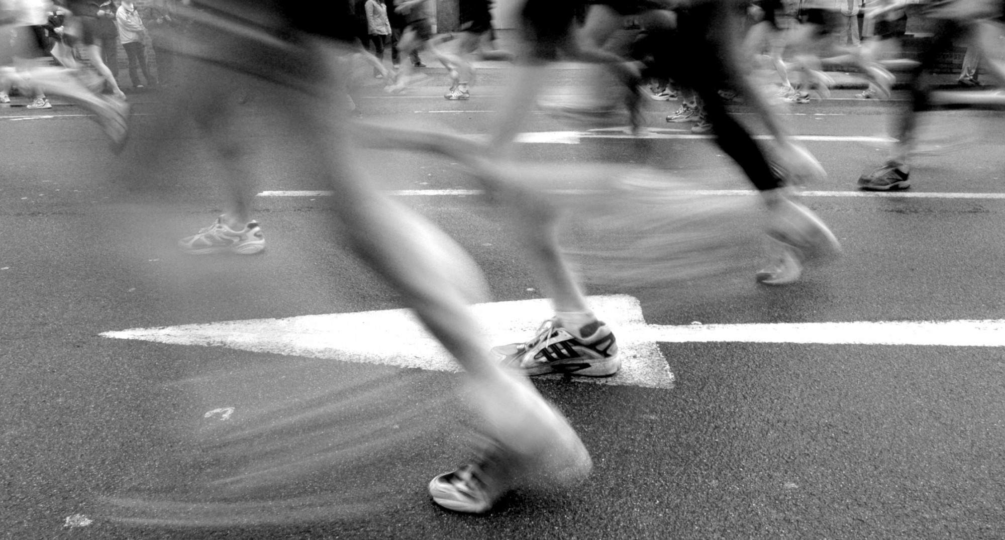 black and white image of runners' legs