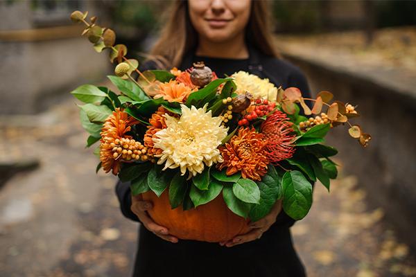 An arrangement of flowers in a pumpkin