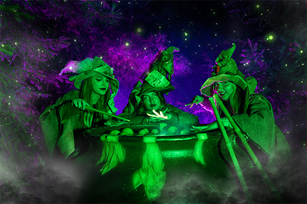 Three witches around a cauldron lit up in bright green