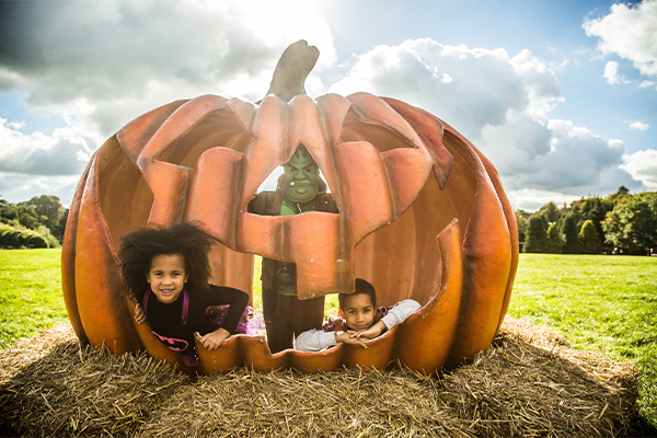 Kids posing in a giant pumpkin outside