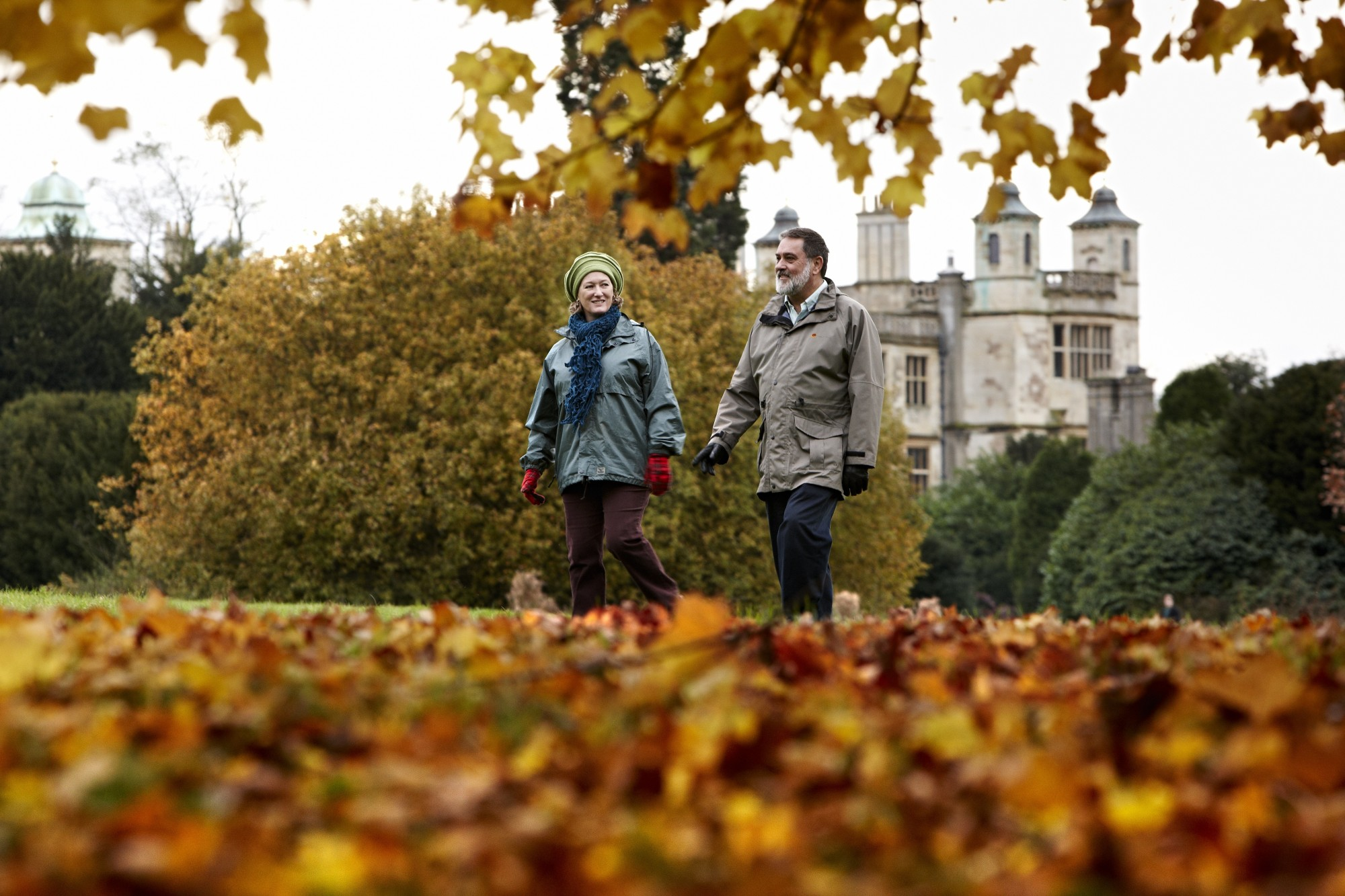 Two women walking across autumn leaves at an english heritage site