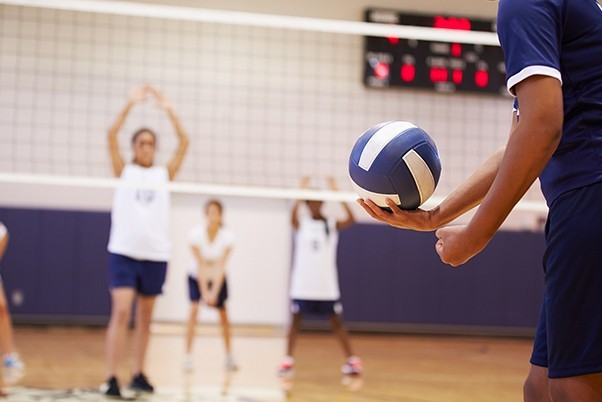 A woman holding a volleyball lining up for a serve