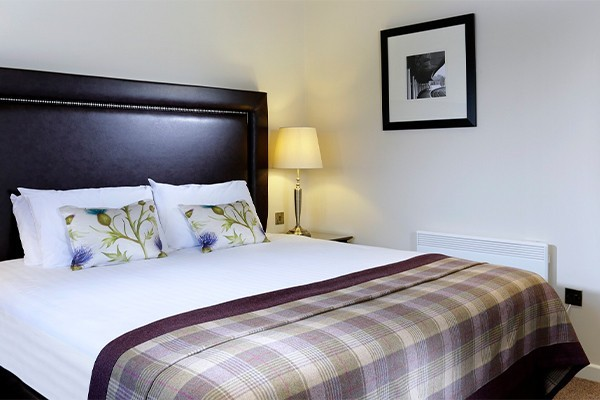 A picture of a double bed in a hotel room at macdonald aviemore resort