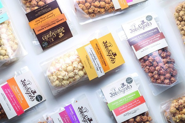 Gourmet popcorn in bags on a white table