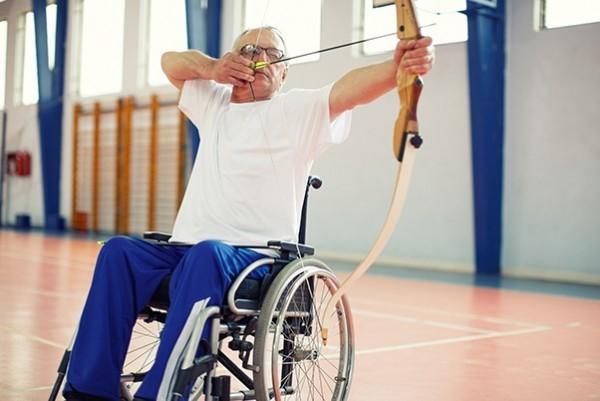 A man doing archery in a wheelchair