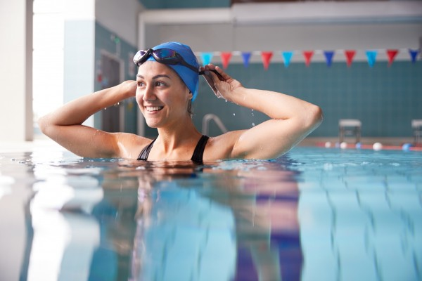 A woman smiling while adjusting her goggles at an indoor swimming pool