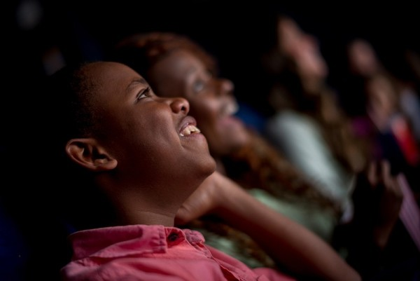 Young boy smiling while watching a movie at the cinema