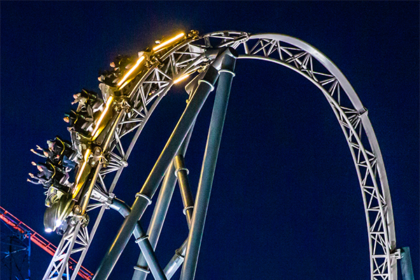 People riding an illuminated roller coaster at blackpool