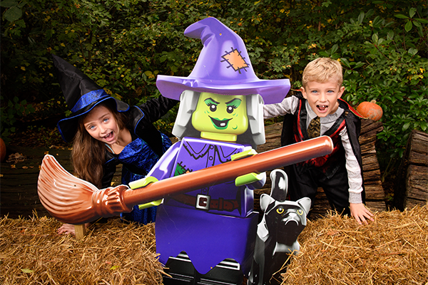 Two kids in halloween costumes post with a large lego witch at legoland