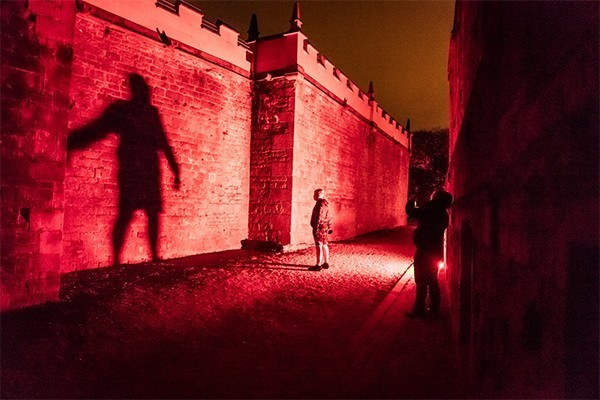 A shadow of a man projected much bigger on an english heritage castle wall with eery red light all around