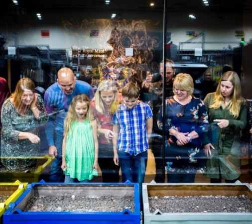 a family looking at old coins at the royal mint tour
