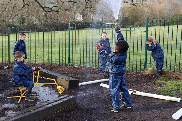 school children wearing waterproof suits and wellies playing with water in a park