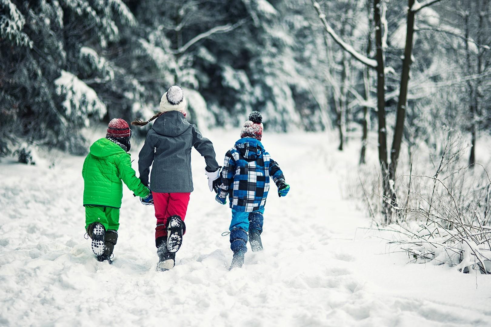 Three children dressed in bright winter clothes run through snowy woods