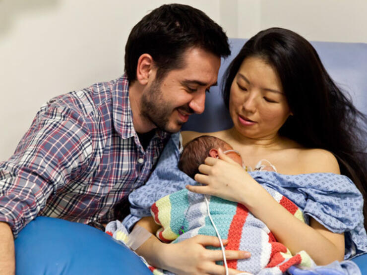 Mum holding baby on a hospital chair with dad alongside looking at baby. Baby is snuggled on mum's chest covered by a blanket.