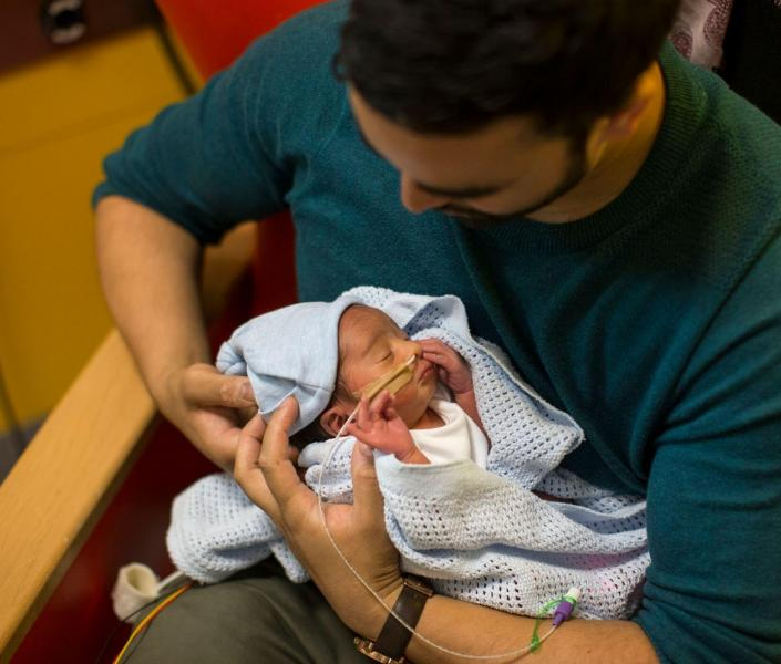 Dad holding baby in hospital
