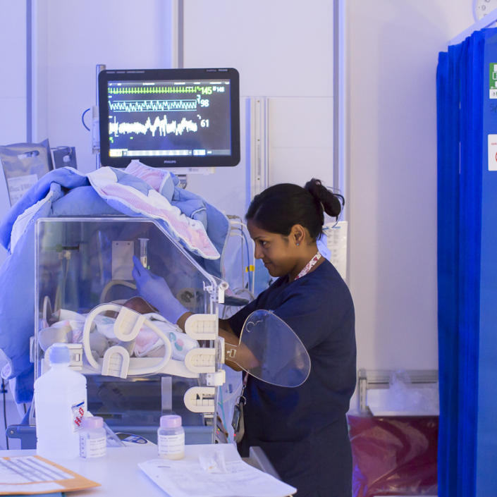 Nurse caring for baby in incubator