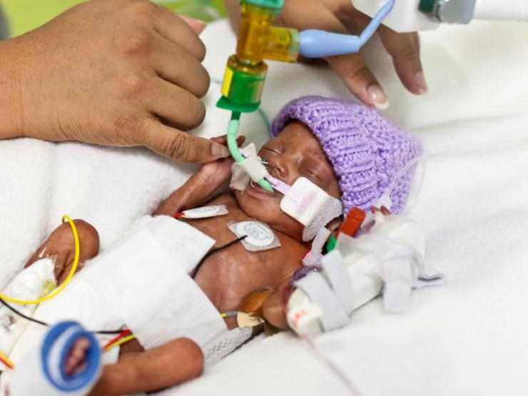 Baby in hospital holding hands with parent