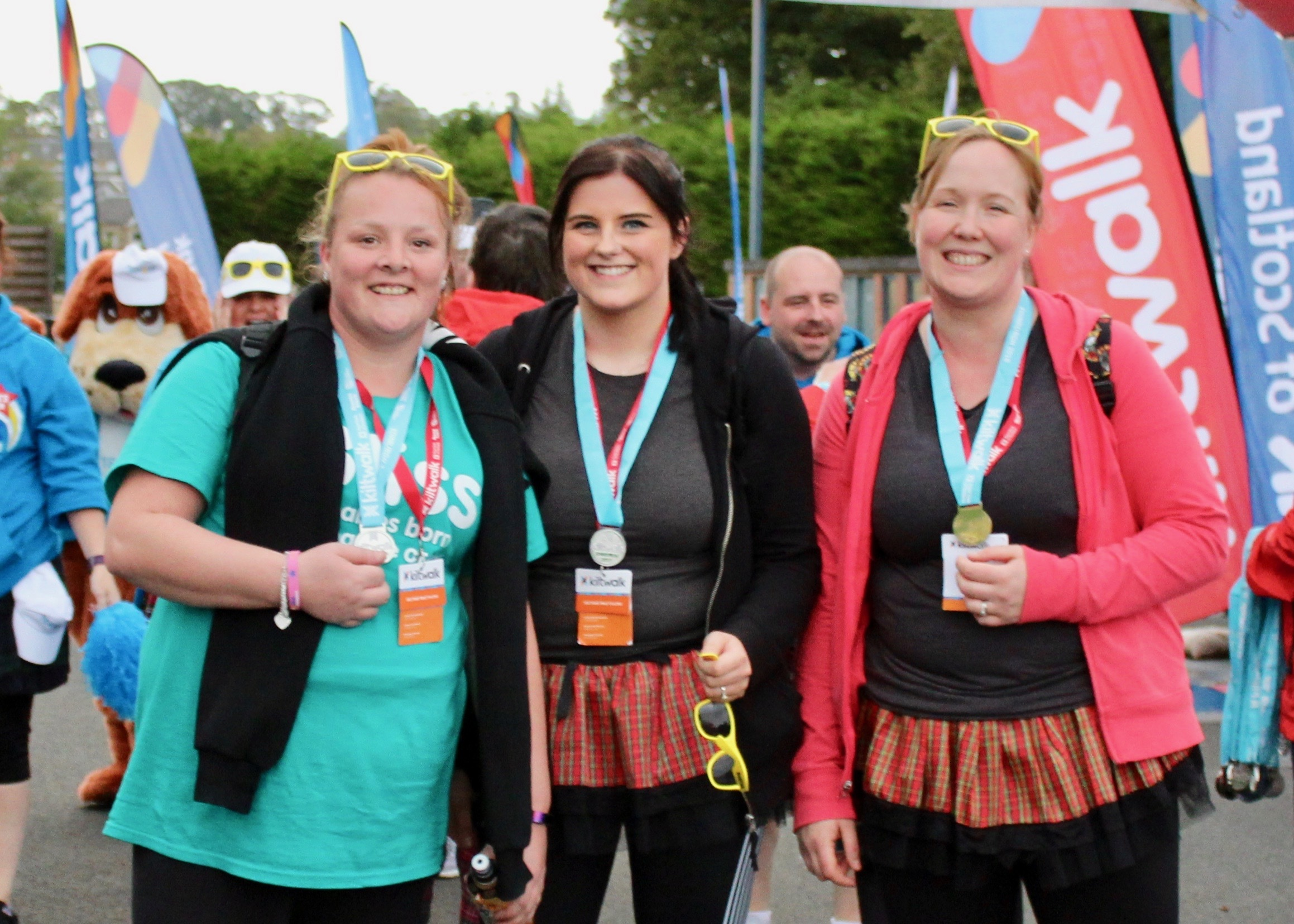 3 women with their kiltwalk medals at the finish line