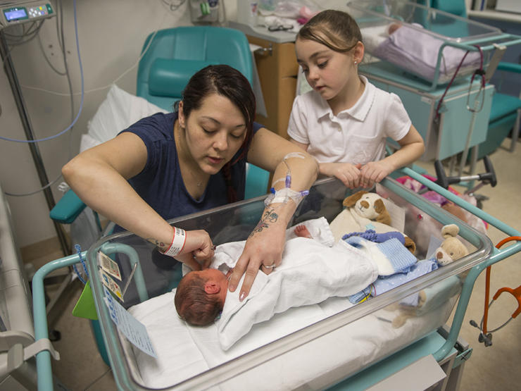 Mum caring for baby with older daughter looking on
