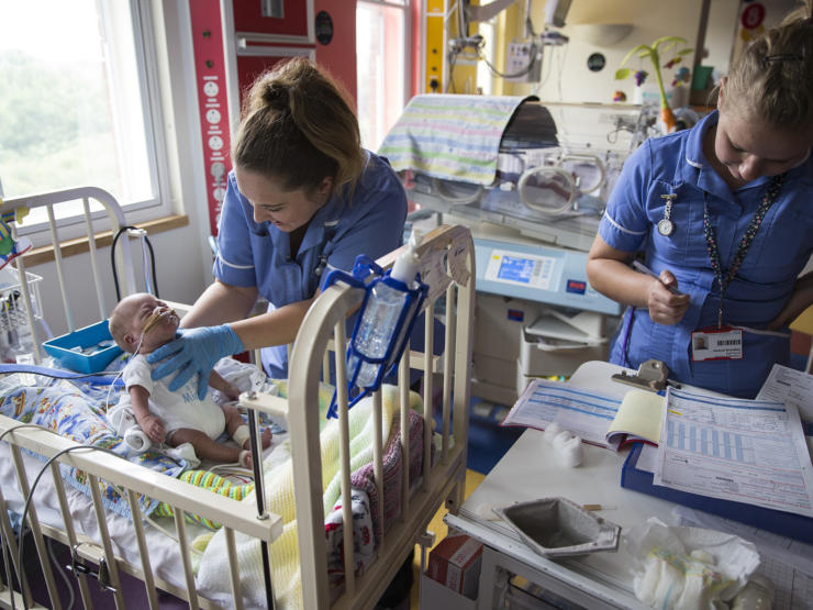 Two nurses, one holding baby up in cot and one looking at paperwork by the side