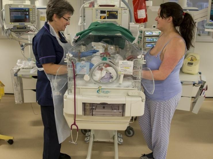 Nurse and mum either side of the cot talking and looking at baby