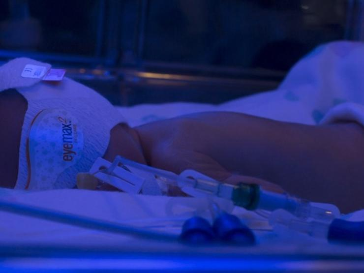 Baby lying in cot with mask on
