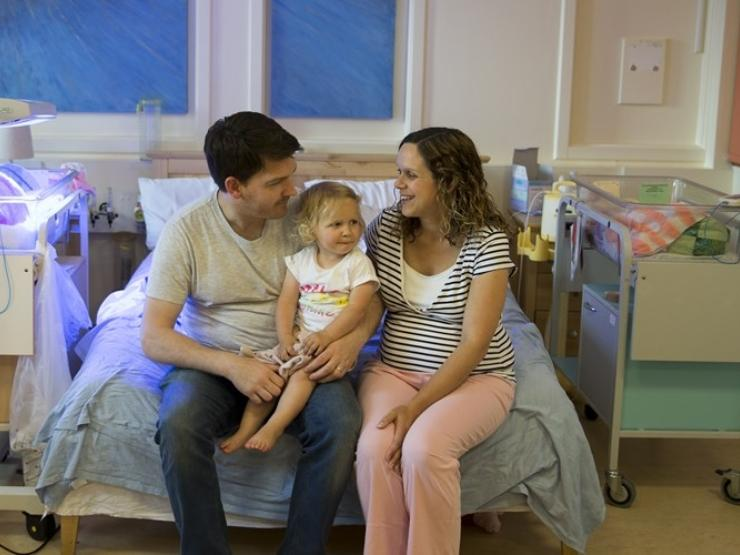 Parents sitting on a bed in hospital with cot beside them and with their toddler on dad's lap