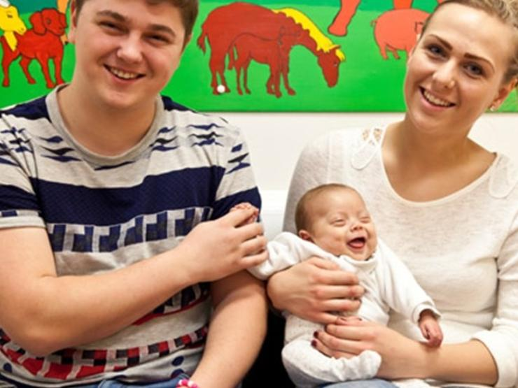 A couple with their baby smiling at camera about to go home