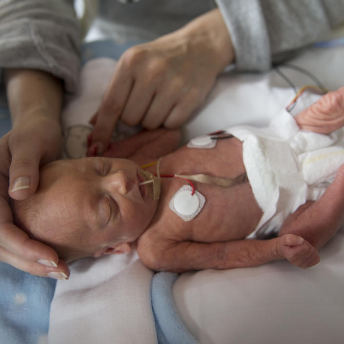 Baby being comforted by parent in hospital